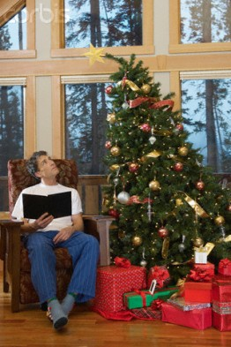 Man looking at leaning Christmas tree